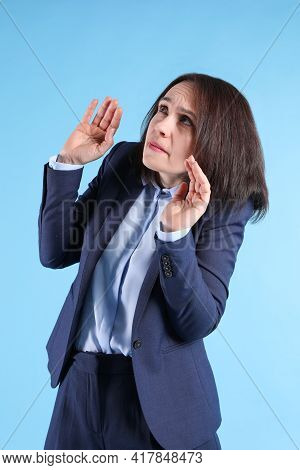 Woman In Suit Avoiding Something On Light Blue Background