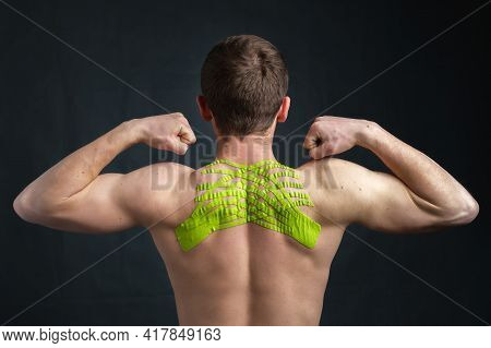 Young Man With Wrinkled Kinesiology Medical Tape On His Neck Applied To Relieve Back Pain Showing Bi