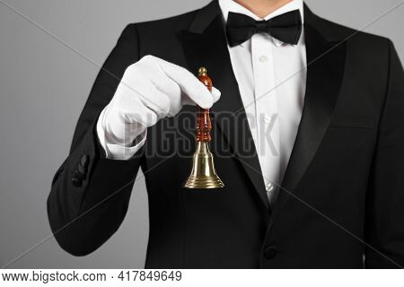 Butler Holding Hand Bell On Grey Background, Closeup