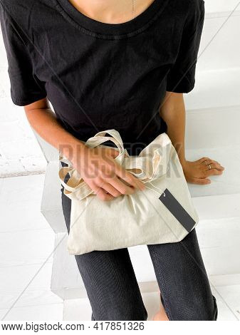 Beautiful Young Woman In Black T-shirt And Jeans Holding A Tote Bag Or Shopper