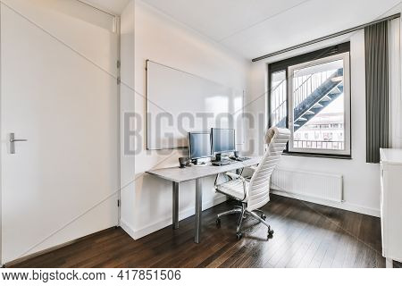 Comfortable Chair Placed Near Desk With Computer Monitors And Whiteboard In Light Workplace In Moder