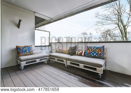 Comfortable Pallet Sofas With Ornamental Cushions Located On Balcony Of Contemporary Flat Against Cl