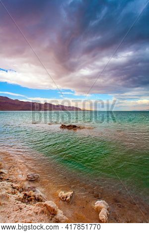 Israel. The picturesque Dead Sea. Winter thunderstorm begins. Low winter clouds are reflected in the green sea water. The healing waters of the Dead Sea