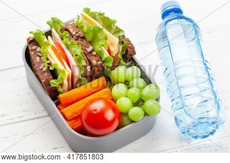 Healthy school lunch box with sandwich and fresh vegetables, water bottle