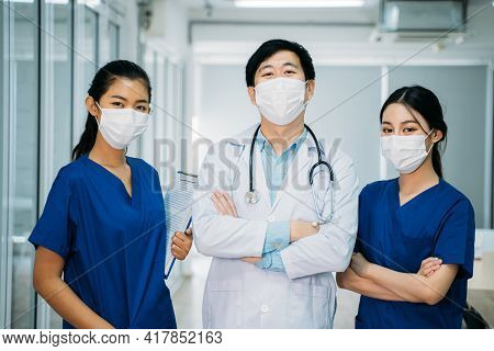 Portrait Of Asian Group Of Male Doctor And Female Nurse In Uniform And Labcoat With Stethoscope And