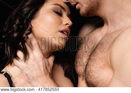 Shirtless Man Choking Sexy Woman Isolated On Black.