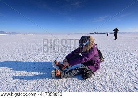 Girl In A Skates For Skating On Ice Sitting On The Ice And Ties It Up