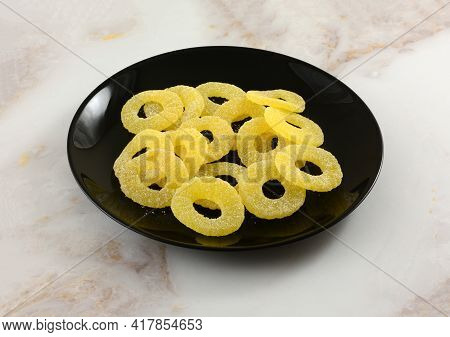 Sour Pineapple Ring Gummy Candy On Black Snack Plate On Table