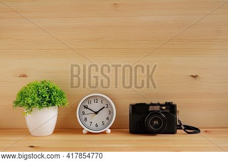Table Clocks And Flower Vases And Film Camera On Wooden Desks. With Copy Space For Text.