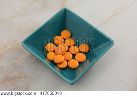 White Chocolate And Caramel Coated Golden Candies In Blue Candy Dish