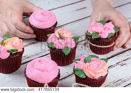 Red Velvet Cupcake With Pink Butter Cream Icing. Confectioner Ourganizing Other Cupcakes.