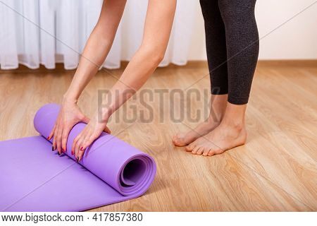 Close Up Of A Womans Hands Is Rolling Up Exercise Mat And Preparing To Doing Yoga. Equipment For Fit
