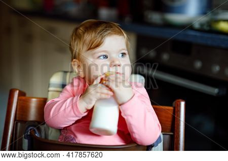 Cute Adorable Baby Girl Holding Nursing Bottle And Drinking Formula Milk. First Food For Babies. New