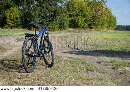 Mountain Bike. Bike Stands On In The Field. A Mountain Bike Stands On A Field Path With Green Grass.