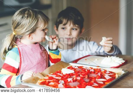 Two Siblings, Little Children Making Italian Pizza At Home. Cute Toddler Girl And School Boy Having
