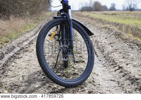 Front Wheel Of A Mountain Bike. Mountain Bike. Stands On A Field Road. Concept Of Cycling, Repair Or