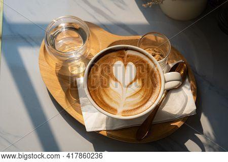 Hot Coffee Latte With Latte Art Milk Foam In Cup Mug On Wood Desk On Top View. As Breakfast In A Cof
