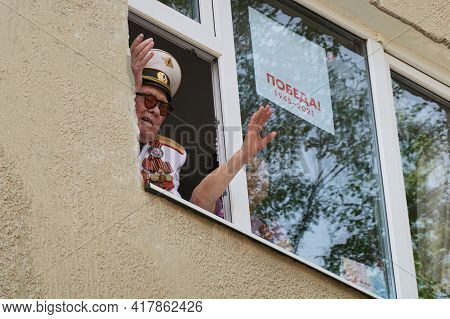 Russia, Nefteyugansk, May 9, 2020: An Old Man In A Tunic With Orders Waves From The Window Of A Hous