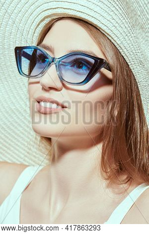 Close up portrait of charming girl in a white dress and elegant hat with wide brim and blue sunglasses looking up on a white background. Sunglasses. Summer fashion.