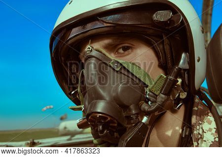 Close-up portrait of a man pilot wearing helmet in cockpit of fighter jet. Military aircraft.