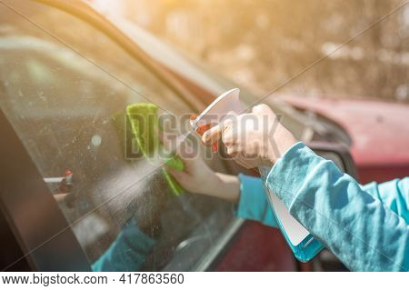 Woman Cleaning Car Windows With Spray Cleaner. Female Hand Cleaning Car Window With Microfiber Cloth