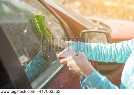 Car Windows Cleaning. Female Cleaning Car Windshield With Cloth And Spray Bottle. Closeup Picture, W