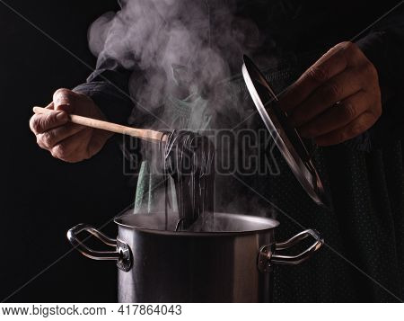 Close-up Open Saucepan Lid, Hands Of Cook And Italian Black Spaghetti On The Background Of A Green A