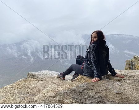 Young Woman Sitting On Edge Of Cliff In Foggy And Cloudy Weather. Female Tourist Enjoys Spectacular
