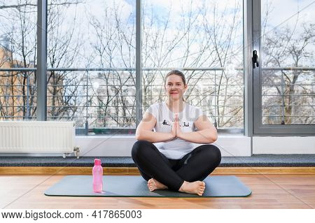 Beautiful Woman Plus Size Sit At Light Sport Gym Hall In Lotus And Namaste Yoga Poses Barefoot With