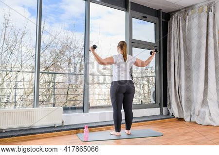 Close Up Plus Size Female Body In White T-shirt And Leggigns Hold Sport Water Bottle On Knee During