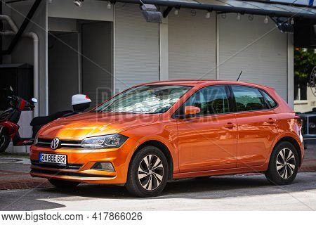 Alanya, Turkey - April 12 2021:  Orange Volkswagen Polo    Is Parked  On The Street On A Warm Summer