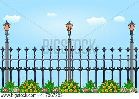 Iron Fence With Street Flashlights And Green Plants. Beautiful Decorative Cast Metal Wrought Fence W