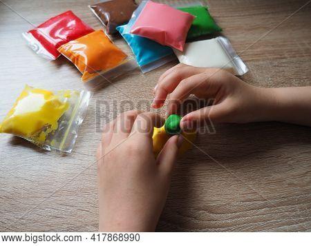 Classes With Plasticine. Children's Hands Crumple Soft Plasticine. Packages With Plasticine Are On T