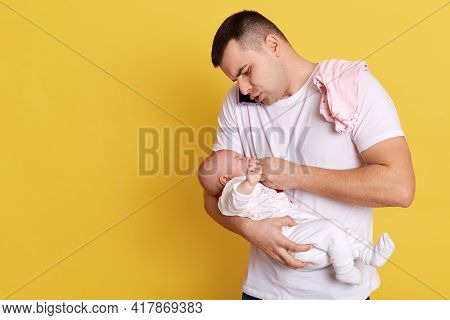 Caucasian Young Father Holding Newborn Baby In Hid Hands, Calming Down Little Kid, Giving Nipple, Ta