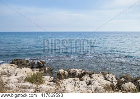 Empty Coastline Of Mediterranean Sea. Coastline Full Of Stones Covered By Salt & Water Weeds. Blue S