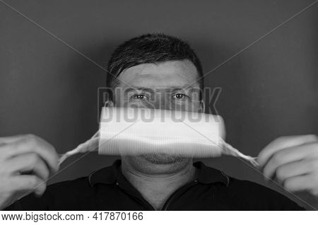 Portrait Of An Adult Male Rotating A Medical Mask In Front Of His Face. A Middle-aged Man With Short