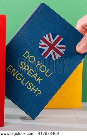 A Man's Hand Holds An Blue English Textbook. Close-up. English Language Day Concept.