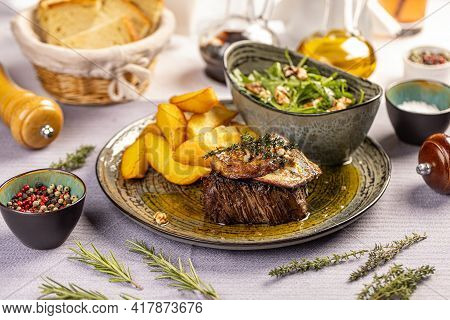 Steak With Grilled Duck Liver Served With Potato Wedges And Aragula On The Restaurant Table