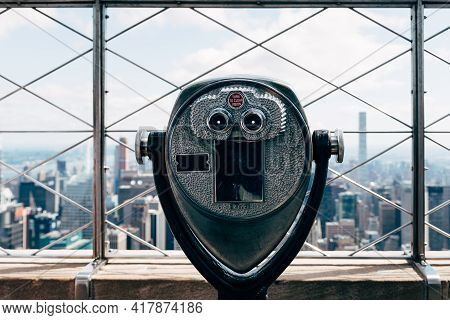 Old Binoculars Against Cityscape Of New York