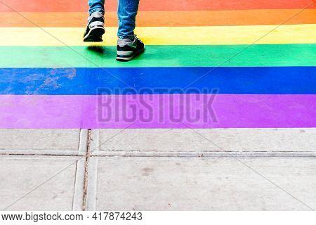 Feet Walking On Sidewalk Decorated With Rainbow Flag