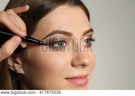 Artist Applying Black Eyeliner Onto Woman's Face On Grey Background, Closeup