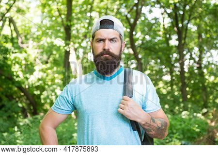 Mature Bearded Man With Beard And Moustache In Summer Shirt And Cap Hold Backpack In Forest, Travele