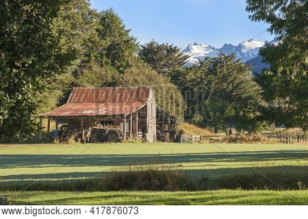 Old Red Farm Shed With Disused Tractors Under Lean-too With Snow-capped Mountains In Background. In