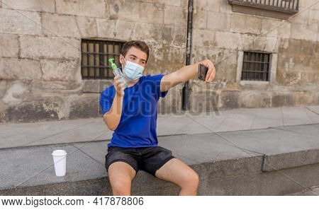 Young Man Wearing Protective Mask Using Hand Sanitizer And Video Calling Friends In The New Normal