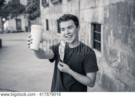 Young Man Wearing Protective Face Mask Walking In The City And Drinking Coffee In The New Normal