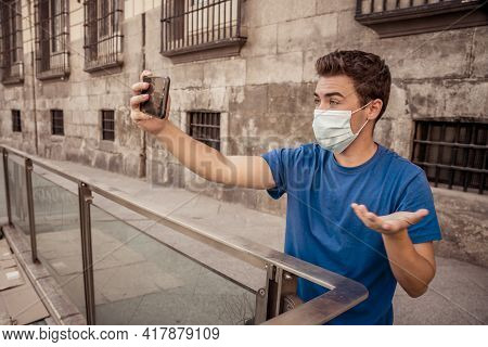 Young Man Wearing Protective Face Mask Video Calling Friends In The New Normal