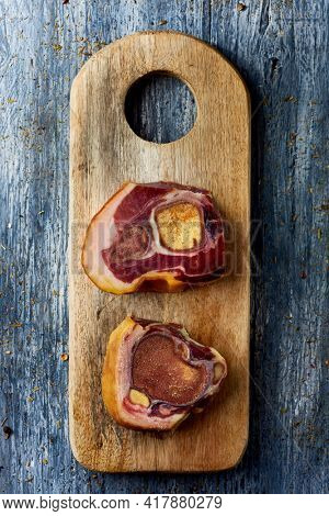 high angle view of some cuts of codillo de jamon, spanish ham hock, on a chopping board placed on a gray rustic wooden table