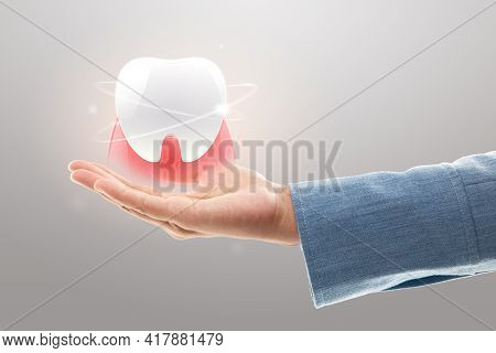 Dentist Hands Showing White Teeth Isolated On A Light Gray Background. Tooth And Gum Care And Protec