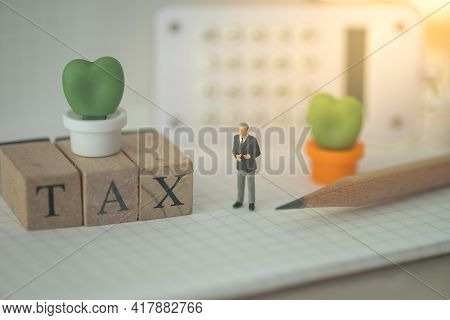 Miniature People : Businessman Stand On Paper And Calculator With Tax Wooden Blocks, Calculation Tax