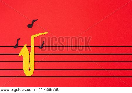 International Jazz Day. Silhouette Of A Saxophone Cutted Out Of Felt, From Which Notes Fly Out, On A